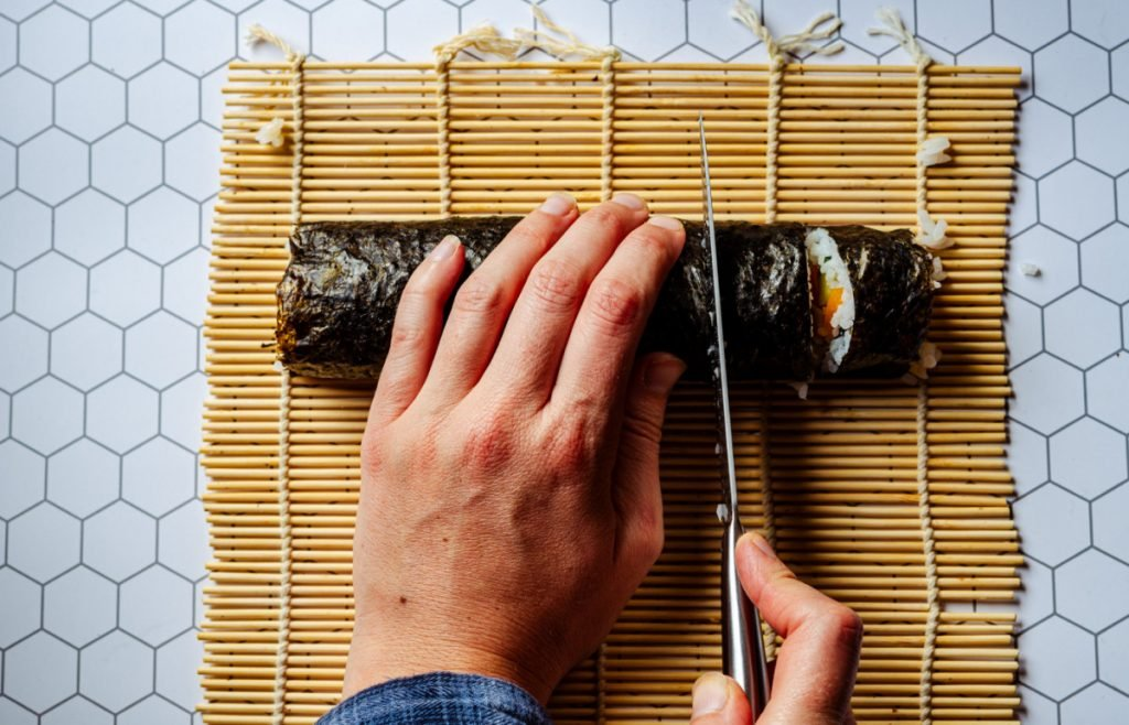Picture showing how to slice sushi. Slice into small pieces with a clean sharp knife.