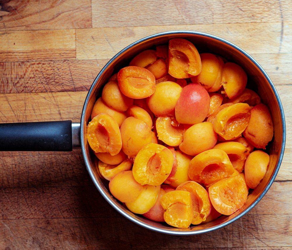 Apricots halved in a large wide saucepan.