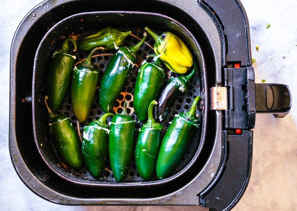 Jalapeno poppers placed in air fryer tray before frying.
