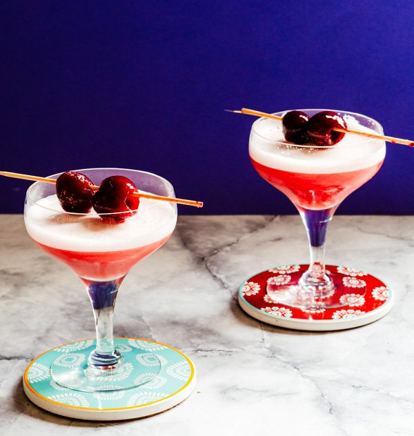 Two Gin cherry sours with cherry garnish served in a coupe glass.