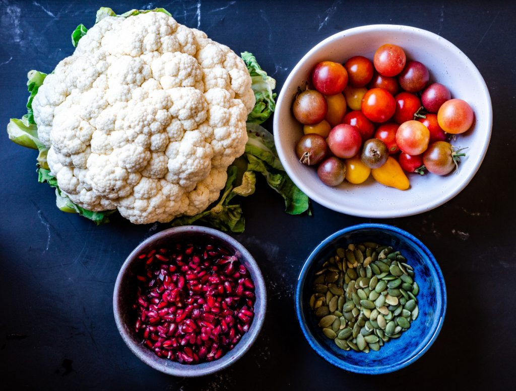cauliflower, cherry tomatoes, pomegranates, pumpkin seeds ingredients for roasted cauliflower salad